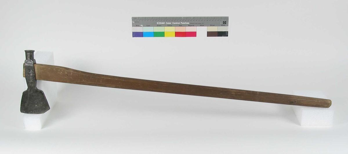 Symmetrisk økseblad.  Øksehodet har en markert rund hammer. Øksehodet har skaftehull. Nytt skaft. Typen har likhetstegn med bondeøks type H.