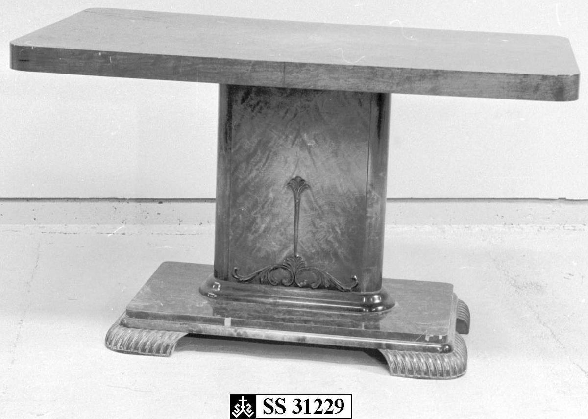 Et bord i furu som er lakkert i brunfarge. Det har firkantet midtsøyle med utskjæring i form av blomst. Midtsøylen står på en plate med fire ben.