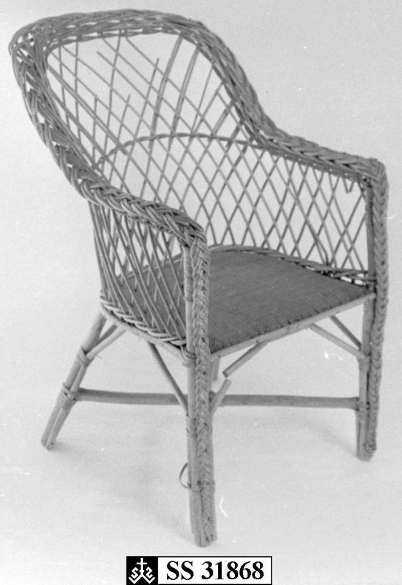 Barnestolen er flettet av manillarør, setet har stoppet rutemønstret  tekstiltrekk.