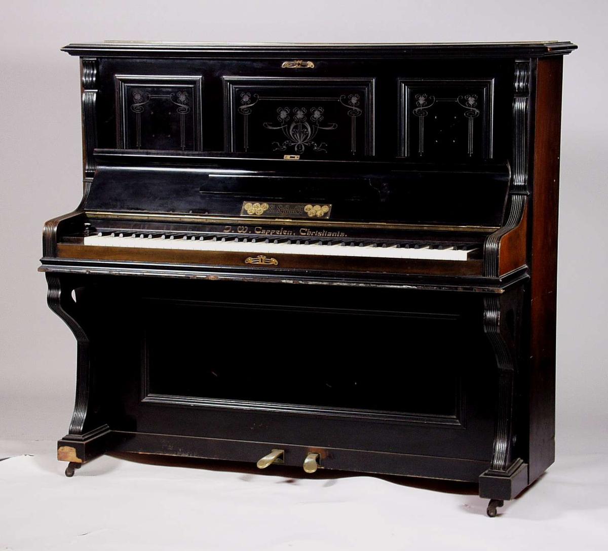 Et svart piano i bjørk og er finért. Det har fyllinger med utskårede blomster og ornament dekor. Langs sidene har pianoet pyntelister som er rillet. Benene er svunge med rillet pyntelister. Pianoet har merker etter kandelaber. Omfang: AAA-a4