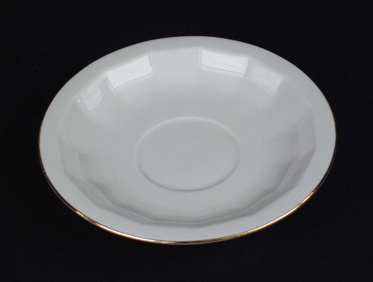 Hvit kaffeskål i porselen med gullkant. Godset har kantet overflate.