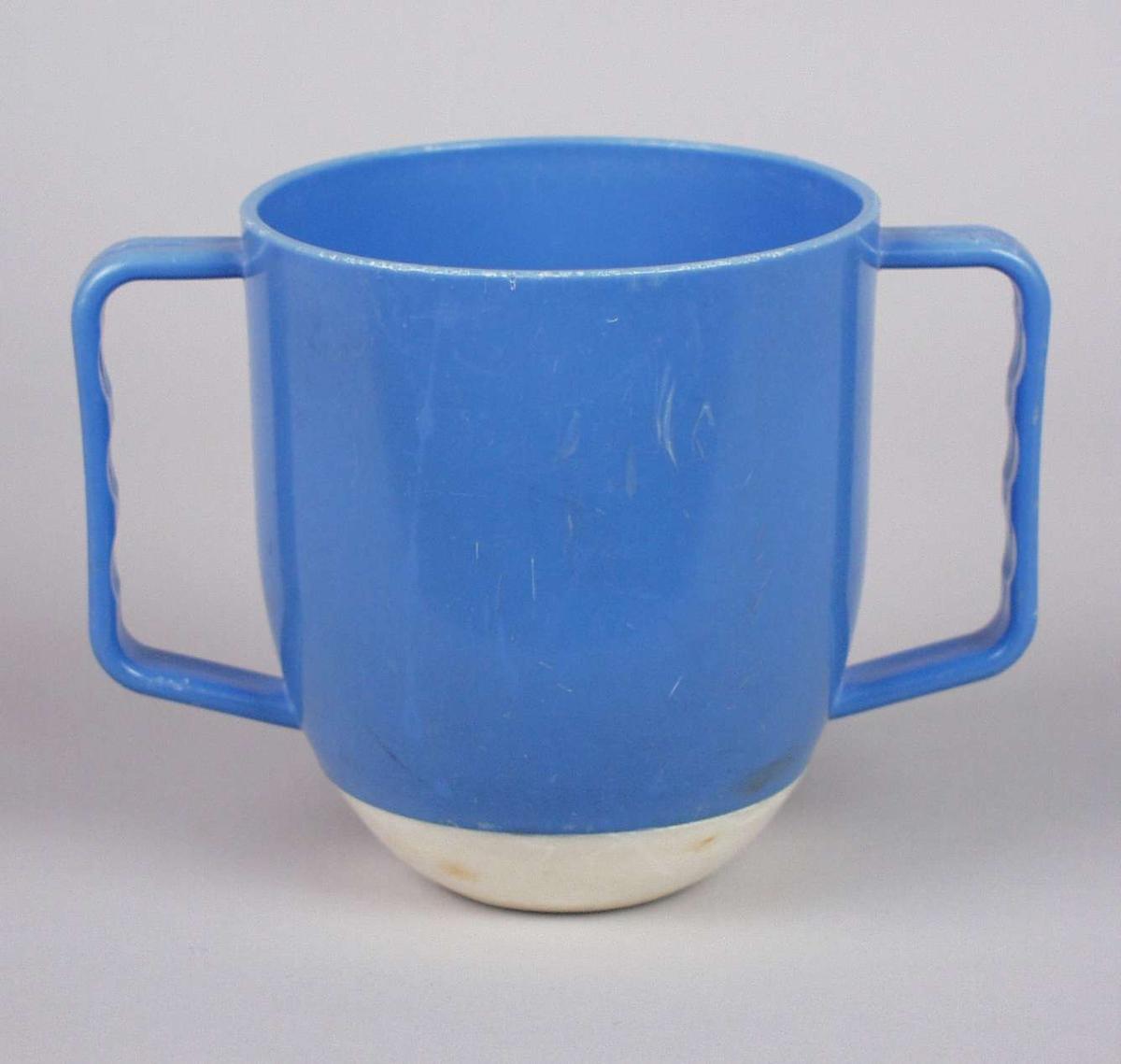 Veltesikker barnekopp i blå plast med hvit bunn. Koppen har to hanker.