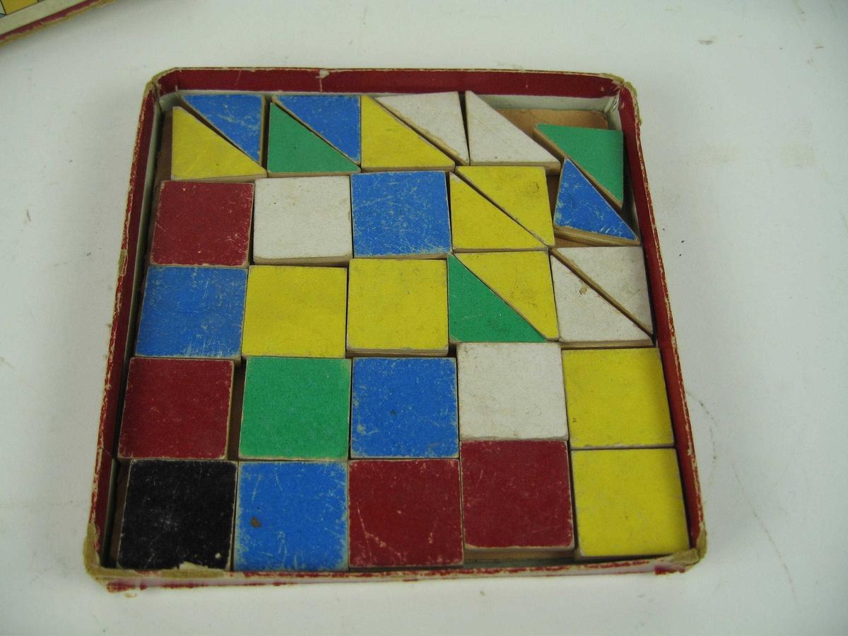 Puslespill i eske. Spilelt består av kvadratiske og trekantede brikker av tykk kartong, med en farge op hver av sidene. Disse kan settes sammen i forskjellige mønstre. Spillet har nå 16 kvadratiske brikker og 13 trekantede. Det mangler en kvadratisk og en trekantet.