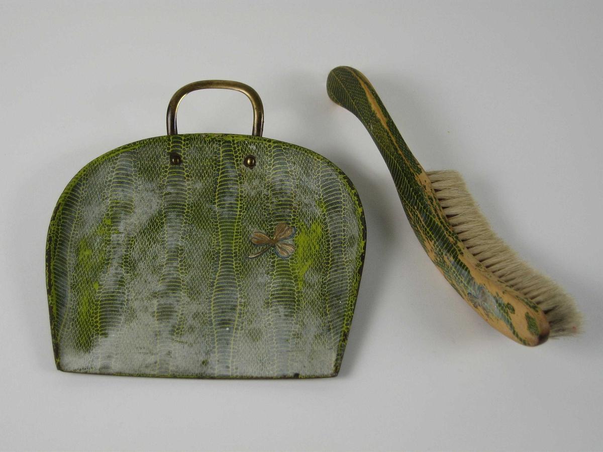 Blikkbrett med påtrykt dekor i grønnfarget slangeskinnsimitasjon, og med en gullfarget trekløver. Tilhørende børste  med treskaft og buet børste.
