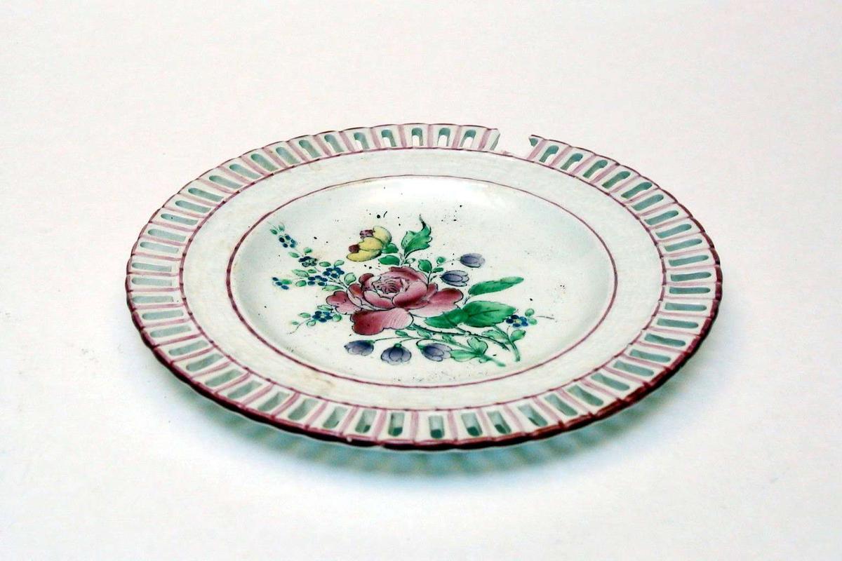 Asjett i keramikk med kremfarget glasur og med polykrom blomsterdekor. Den har 'hullfallskant'. Stemplet er: K et G, Lunéville, France. Det er preget et symbol (en lorgnett) i godset. Asjetten er defekt.