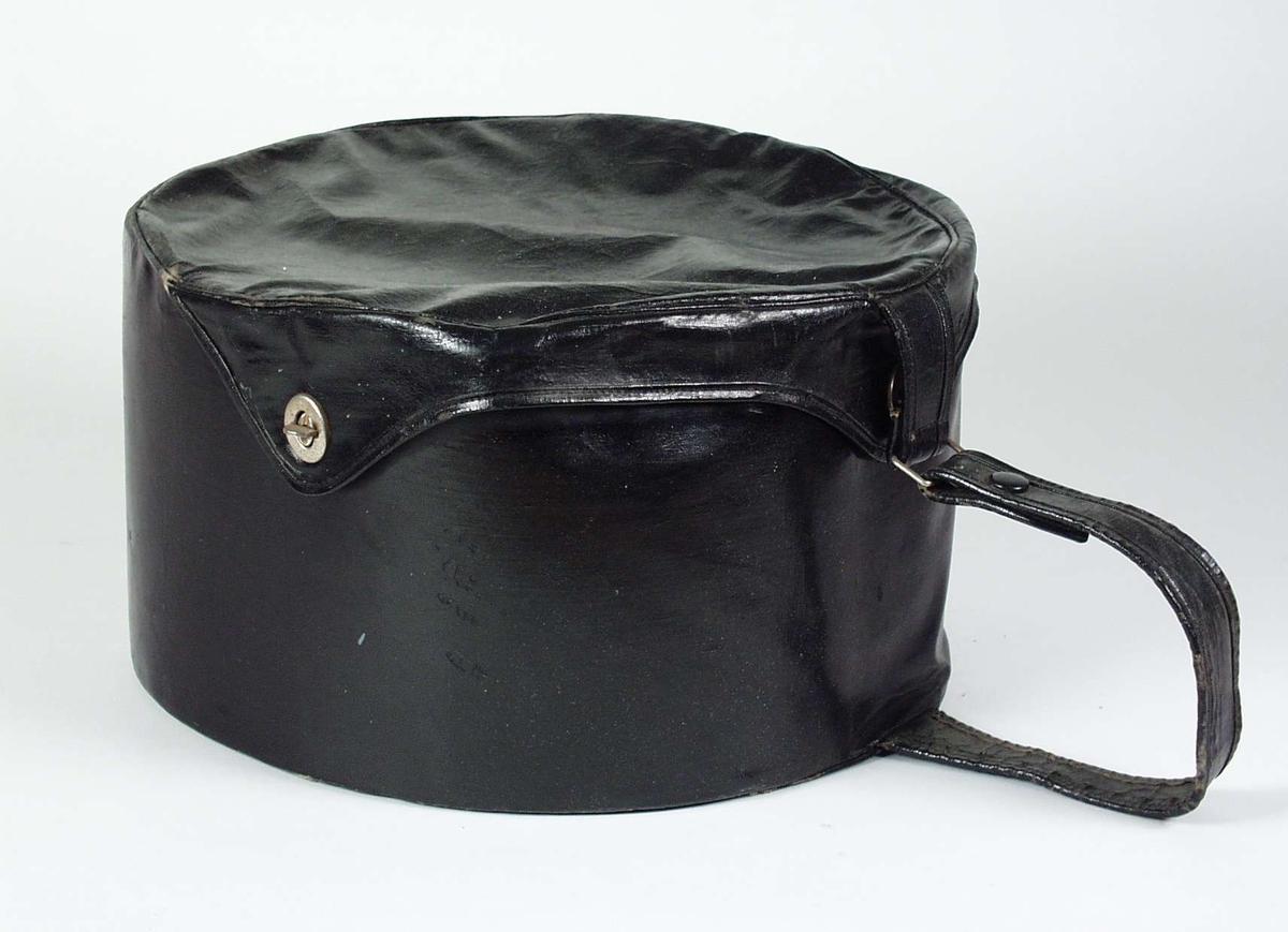 Rund hatteeske av kunstlær. Den er trukket med tekstil innvendig og har 4 snorer som er festet i bunnen. Lokket er delvis festet til esken. Lokket har lukkemekanismer i metall. Esken har håndtak.