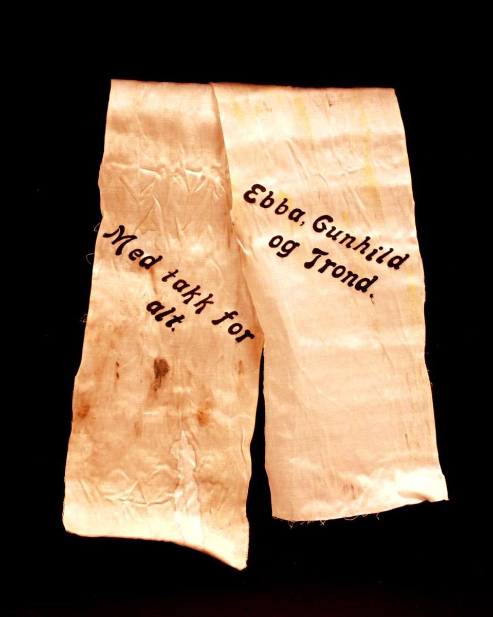 Bånd i kremfarget silke. Båndet er delt i to. På båndet står: Med tak for alt. Ebba, Gunhild og Trond.