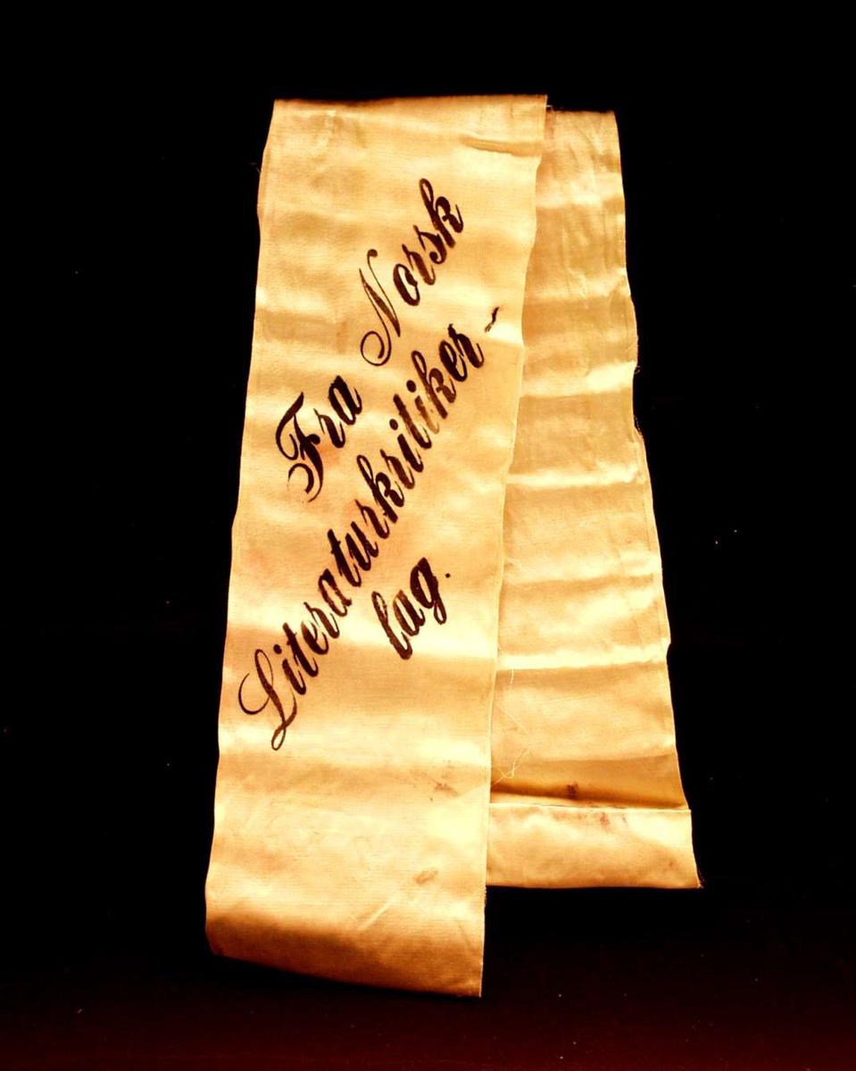 Bånd i falmet grønn silke. På sløyfen står det skrevet: Fra Norsk Literaturkritikerlag.
