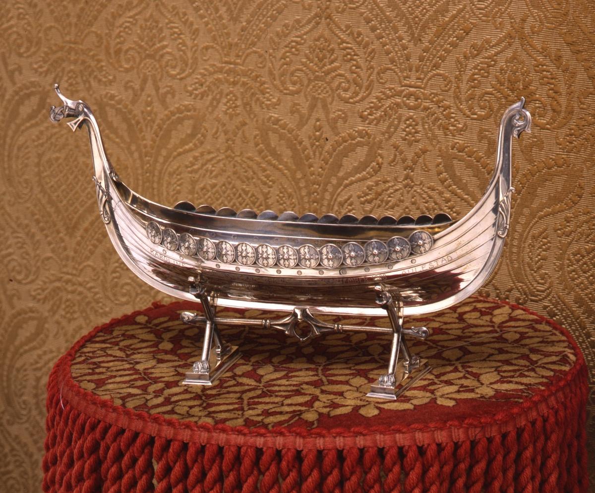 Støpt vikingeskip i sølv med dragehoder og skjold. Understellet har kryssende ben som ender i løveføtter, tversprosse og to profilerte fotstykker