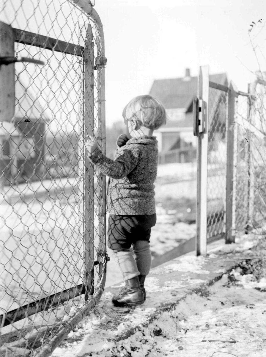 Vinter. Liten gutt i porten til lekeplassen. Gunnar Berge.