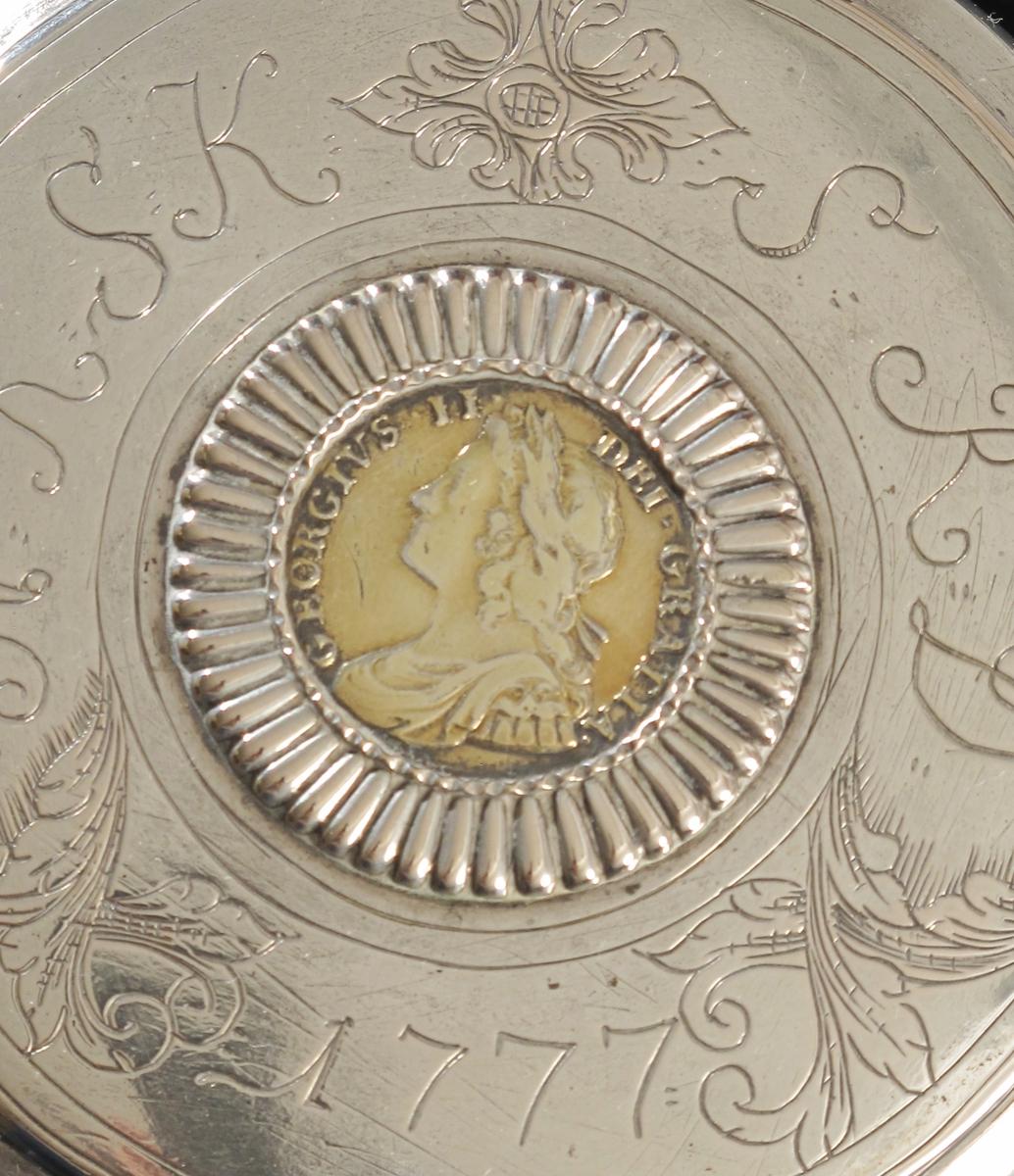 """Stentøykrus m. sølvlokk.  Flatt lokk, rundet, profilert kant, på lokket  graver eierinitialer og årstall. mellom akantusblad. I midten mynt i radiært riflet innf. : Profilhode  og innskr.:   GLORGIUS II DEI GRATIA, reversen har  4 våbenskjold stilt i kors m. rosetter mellom og  """"ordenskors"""" i midten, samt innskr.:  A T. ET. E. 1734. M. B. F. ET. H. REX.   F.D.B. ET. L. D. S. R. I.  Som lokkgrep blad m. opprullede fliker.   Lokket montert på stentøykrus,  sylindrisk, nederst  bredt rillet feldt, brunt, deretter glatt, så  rillet lyst feldt, hanken buet."""