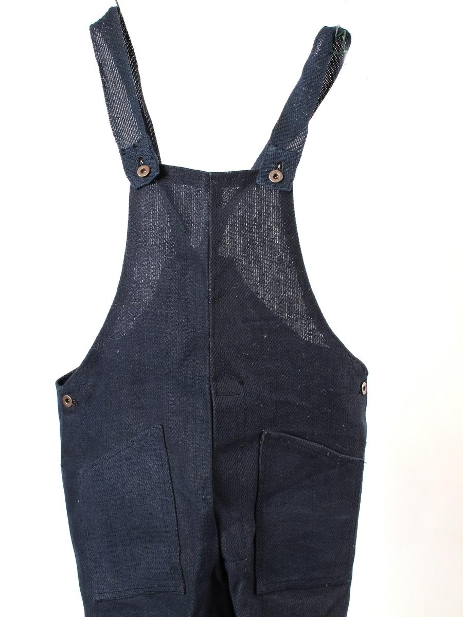 Overall,  fra krigen 1940-45. Papirtekstil. laget av tøy vevd at papirstrimler. Mørkeblå.  Overall til en kort og bred person, sort   maskinsøm.  Ubrukt.   Tilstand : god.