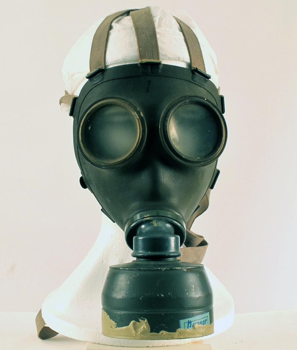 """Gassmaske,   Folkemasken"""",  Norsk Sivilforsvar  1940. Askim Gummivarefabrikk.   gummi, Metall, celluloidglass, lerretsremmer.    Klokkeformet metallbunn med gummifilter under.  Ansiktsmasken er festet på skrå i forhold til filteret. To sirkulære glass, grå  1940,  mellom øynene: 1. Delvis skjult lysblå etikett  nederst, tekst:   PANSER.   Tilstand: god."""