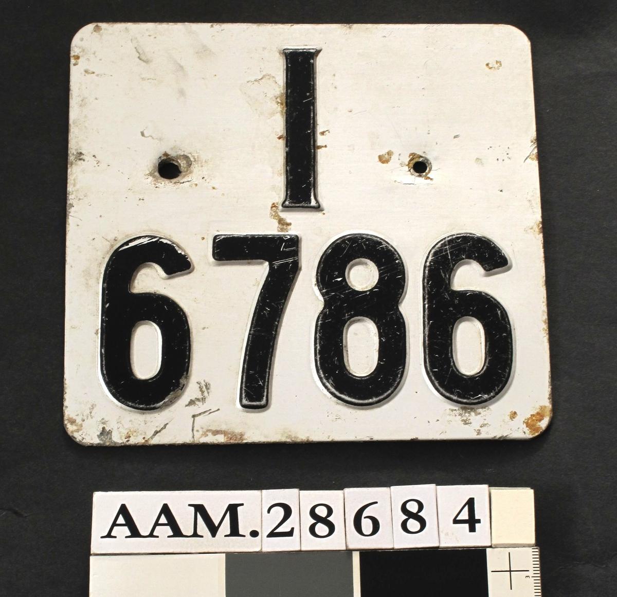 Nesten kvadratisk skilt, blank flate med sort bokstav og siffer. Bokstaven I (for Aust-Agder) øverst og sifrene 6786 under. Denne type kvadratiske skilt var vanligvis brukt på mopeder og motorsykler.