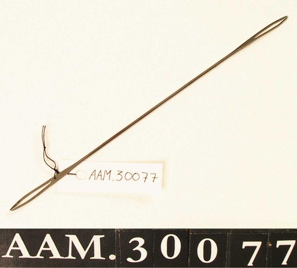 Form: Lang nål. I begge ender to spisser som er bøyd mot hverandre, slik at det dannes en spalte. Et lite hull bak den ene spalten.