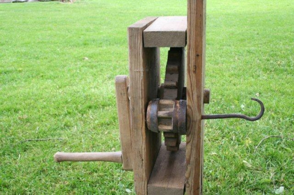 Planke med påmontert kasse. Inni denne et  tannhjul som drives med en sveiv. Jernkroken fungerer som akslingr for tannnhjulet. Kasse av furu, tannhjul og sveiv av bjørk. Føyd sammen med runde plugger.