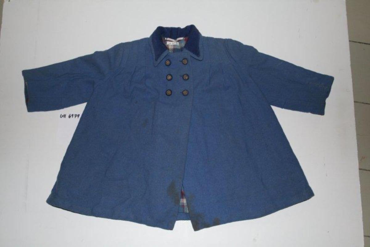 Barnekåpe, utsvingt/ utskrående. Seks knapper med gulldekor lukker jakken. Cordfløyel på krage og flanellstoff på fôret inni jakken. Splitt bak.