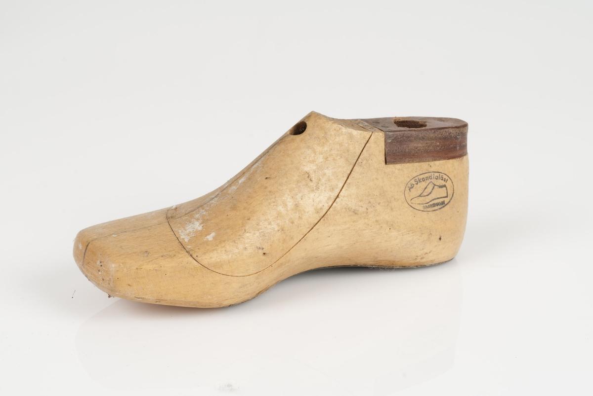 En tremodell i to deler; lest og opplest/overlest (kile). Høyrefot i skostørrelse 28 med 8 cm i vidde. Halve sålen av metall. Lestekam av skinn.