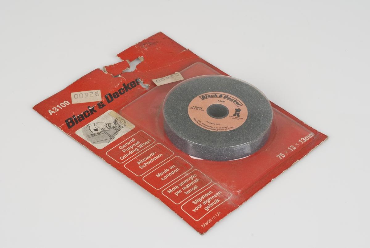 Rund slipestein til pusse/slipemaskin. Slipesteinen ligger i en rød papp-/plastpakning Rosa merkelapp på slipesteinen.
