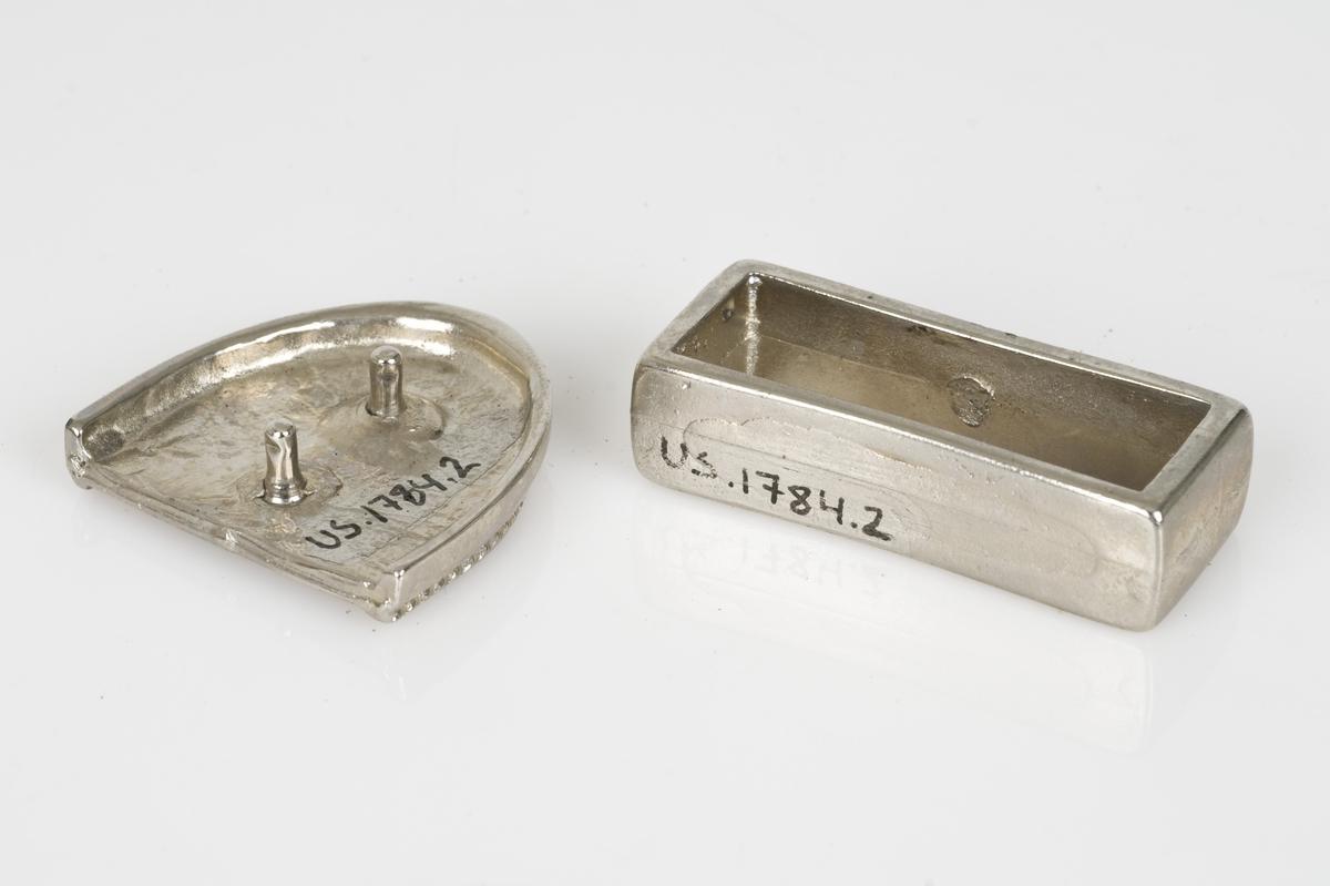 Består av to deler (A-B) til belte av metall. Mønster på beltespennen.
