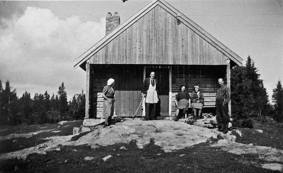 Kvinner og menn utenfor et tømmerhus.