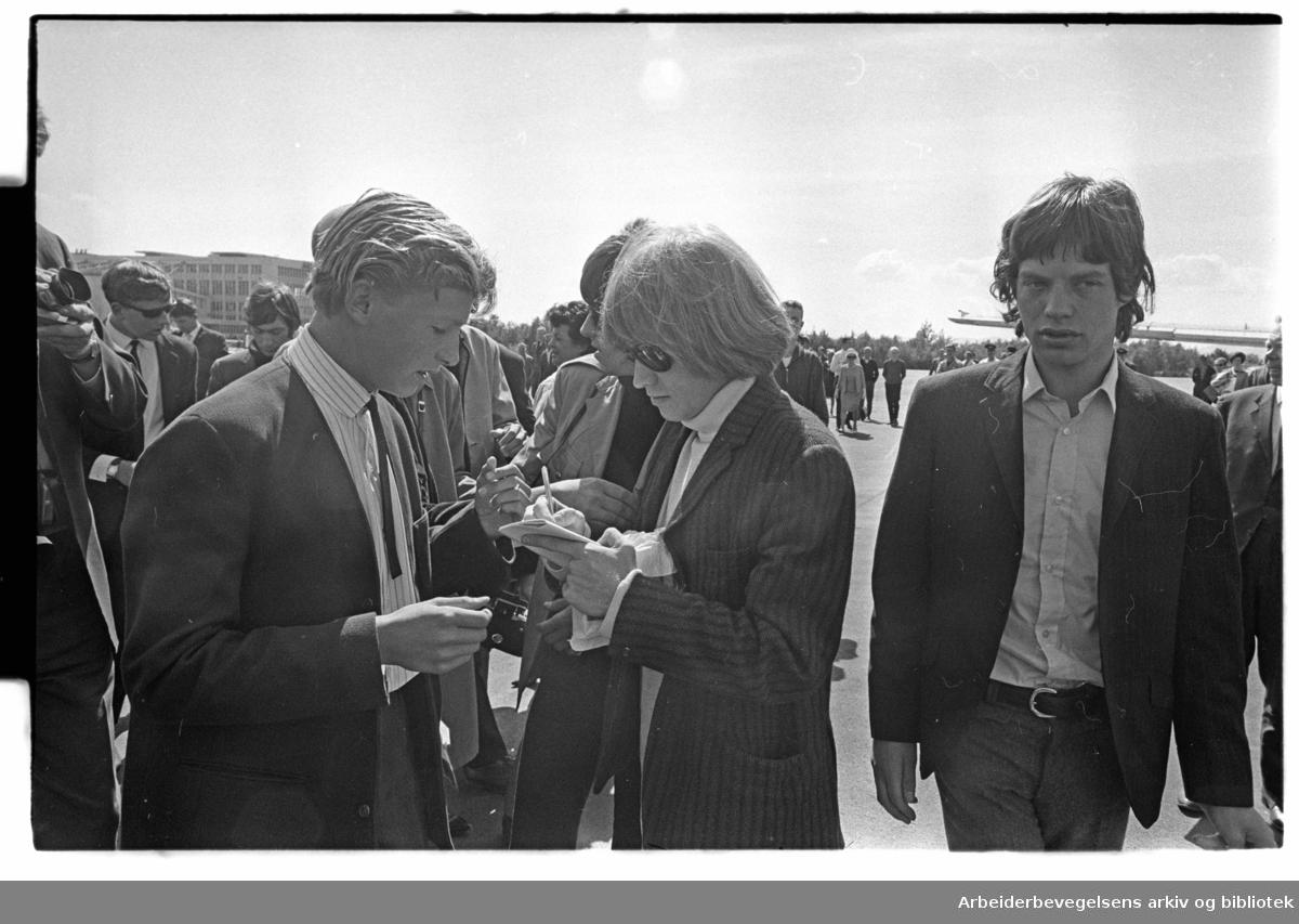 The Rolling Stones ankommer Oslo, via Fornebu flyplass, 23. juni 1965. .Brian Jones skriver autografer. Mick Jagger til høyre..
