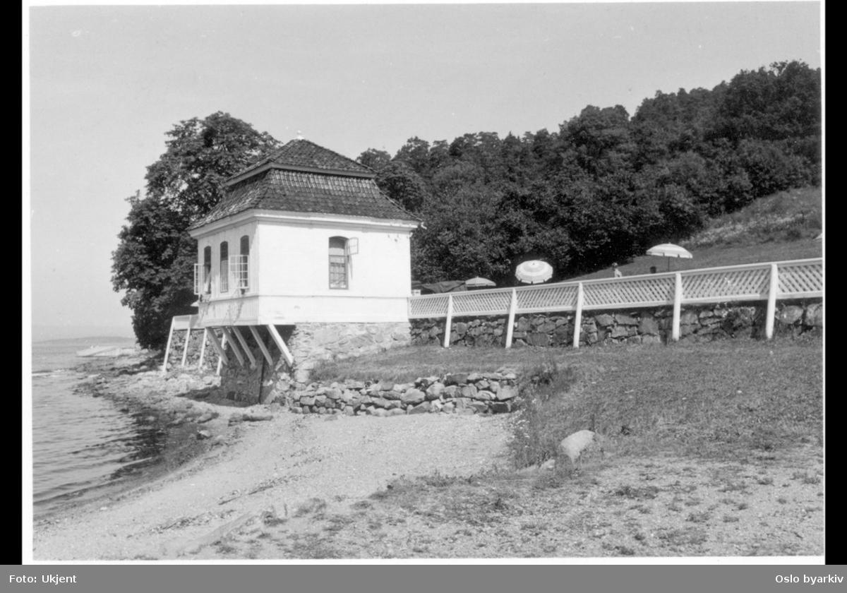 Det tidligere lysthuset (rokokkopaviljongen) til Stubljan gods, sett fra badestranden. Nå kiosk og kafé (uteservering) for Hvervenbuktas badegjester. Parasoller.