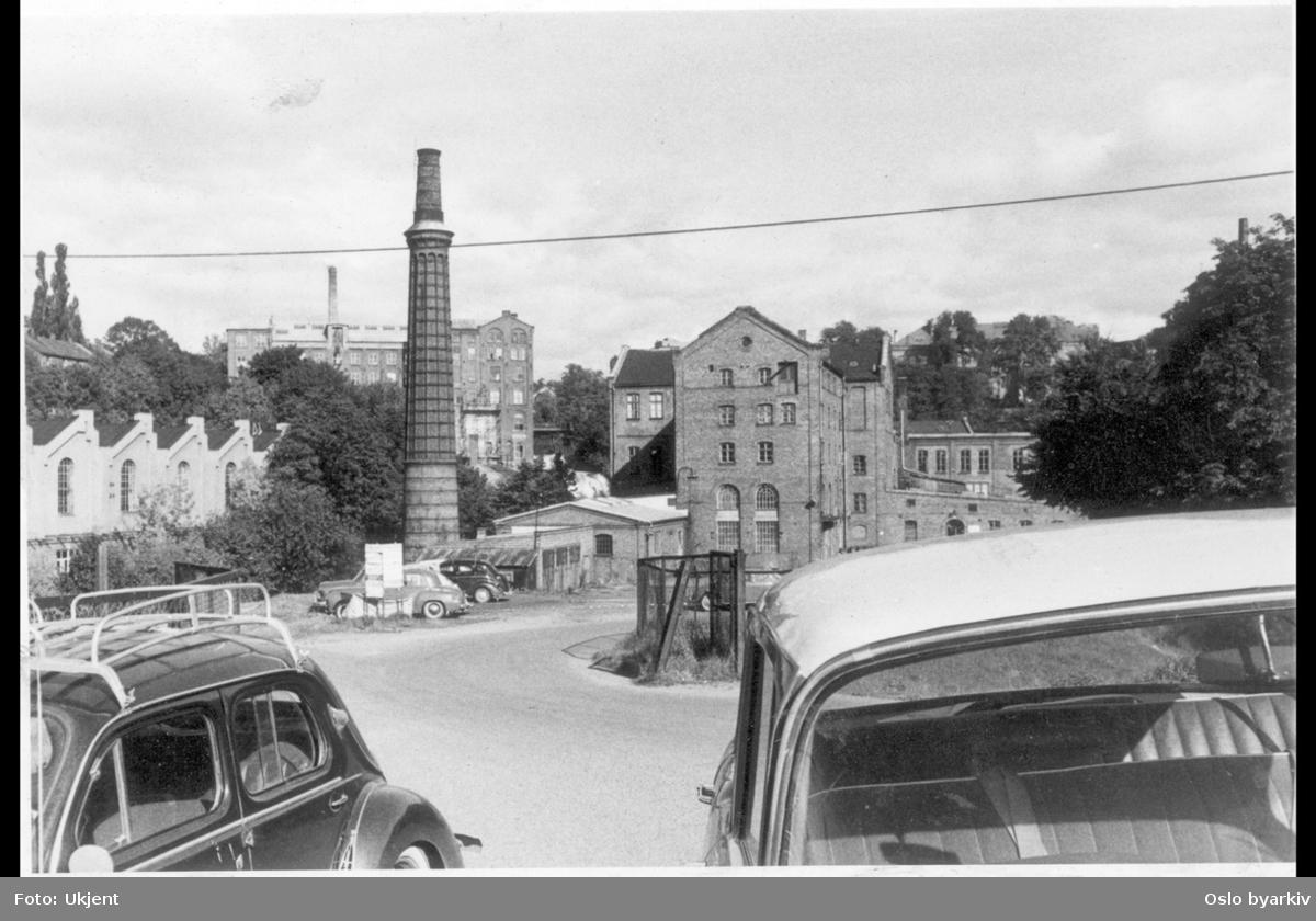 Ved Akerselvas østre bredd nordover med Foss bryggeri sine lokaler og pipe. Til venstre for pipa Sagveien 2. Bak pipa ses Graahs spinneri og Vøienfallene. I front pakeringsplass med to parkerte biler, Renault 4 CV og Opel.
