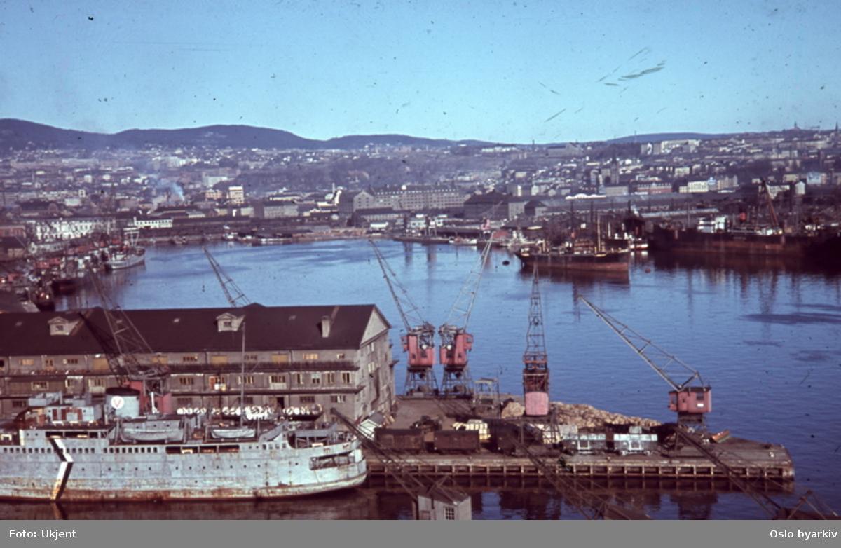 """Utsikt over Bjørvika fra toppen av kornsiloen på Vippetangen. Båter ved kai, nærmeste er Larvikferga """"Peter Wessel"""". Havnekraner. Sannsynligvis fotografert av tysk soldat under krigen."""