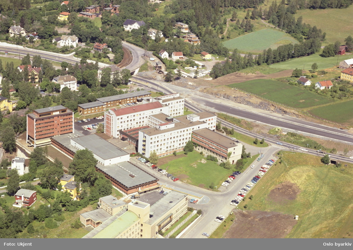 SINTEF bygget. Harald Schjelderups hus og Forskningsveien i front. Slemdalsveien og Trikkesporet til Holmenkollbanen går i bro over Ringveien i bakgrunnen.  (Flyfoto)
