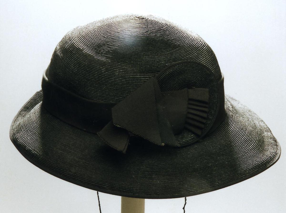 Hatten har smale striper sydd sammen fra runding i midten. Tilnærmet rund pull, bremmen noe bredere foran enn bak. I overgang pull/brem et 3, 5 cm. bredt svart ripsbånd. Midt foran, festet til ripsbånd, rund dekor, ca. 9 cm. diameter, i stråmateriale, dobbelt ripsbånd tredd gjennom midten, ut til høyre siden. Inne i hatten i overgang pull/brem, et rips-silkebånd 2 cm. Rund strikk festet i hver side. I følge opplysninger fraq modist Dagny Nordby, Hamar, var dette materialet ikke av det rimeligste stråmaterialet.