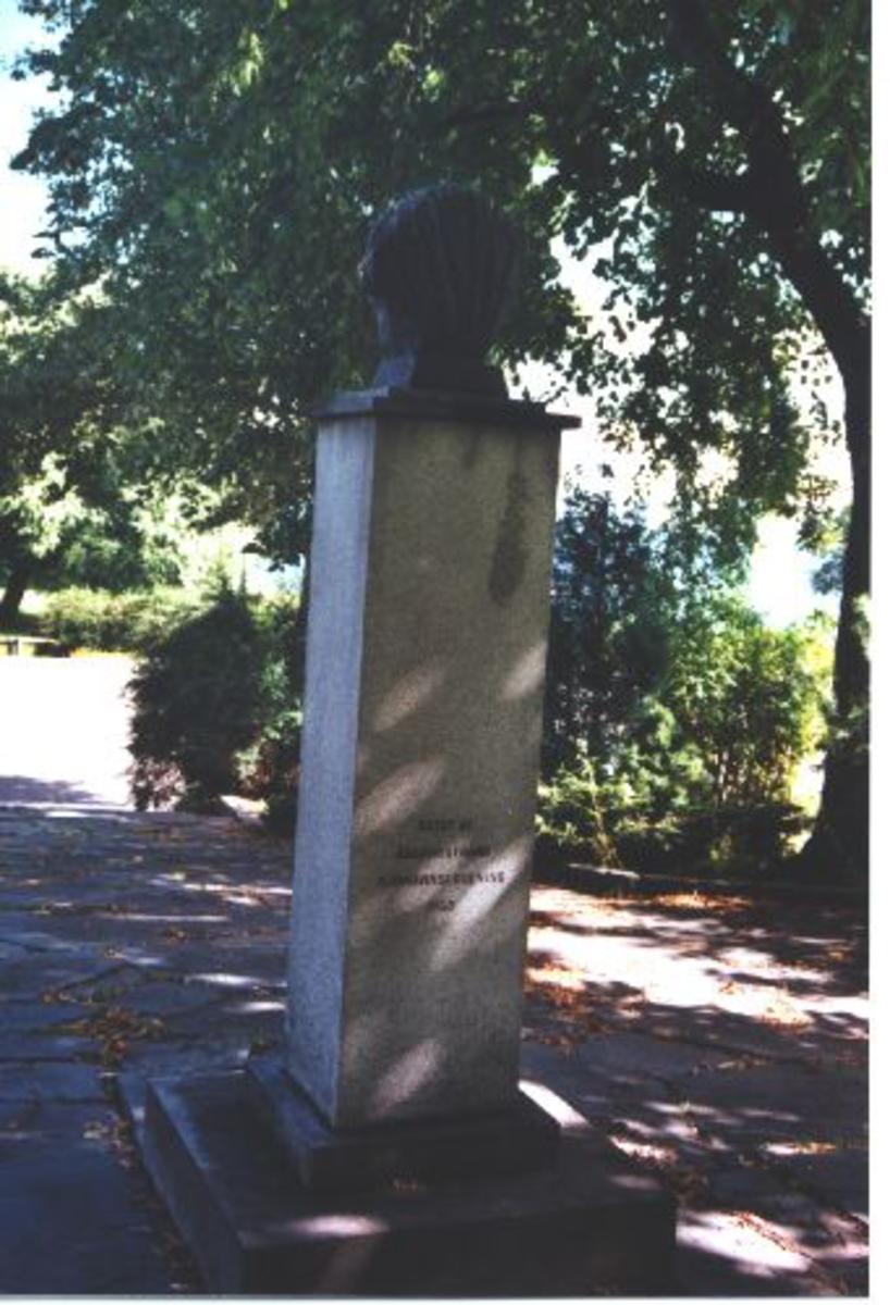 Skulptur av seilskute inne i noe som ligner et skjell, på sokkel av lys granitt.
