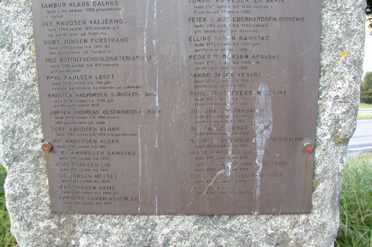 Ca 4 m høy bauta med innhugd tekst og kopperplate med inskripsjon