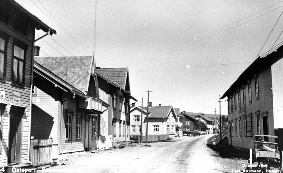 Oversikt Gamlegata, Brumunddal. Til venstre Heimdal Kafe, skomaker A.Andersen, Sørheim, Mamre Lund, Bakken gård, Brumunddal Frørenseri til høyre.