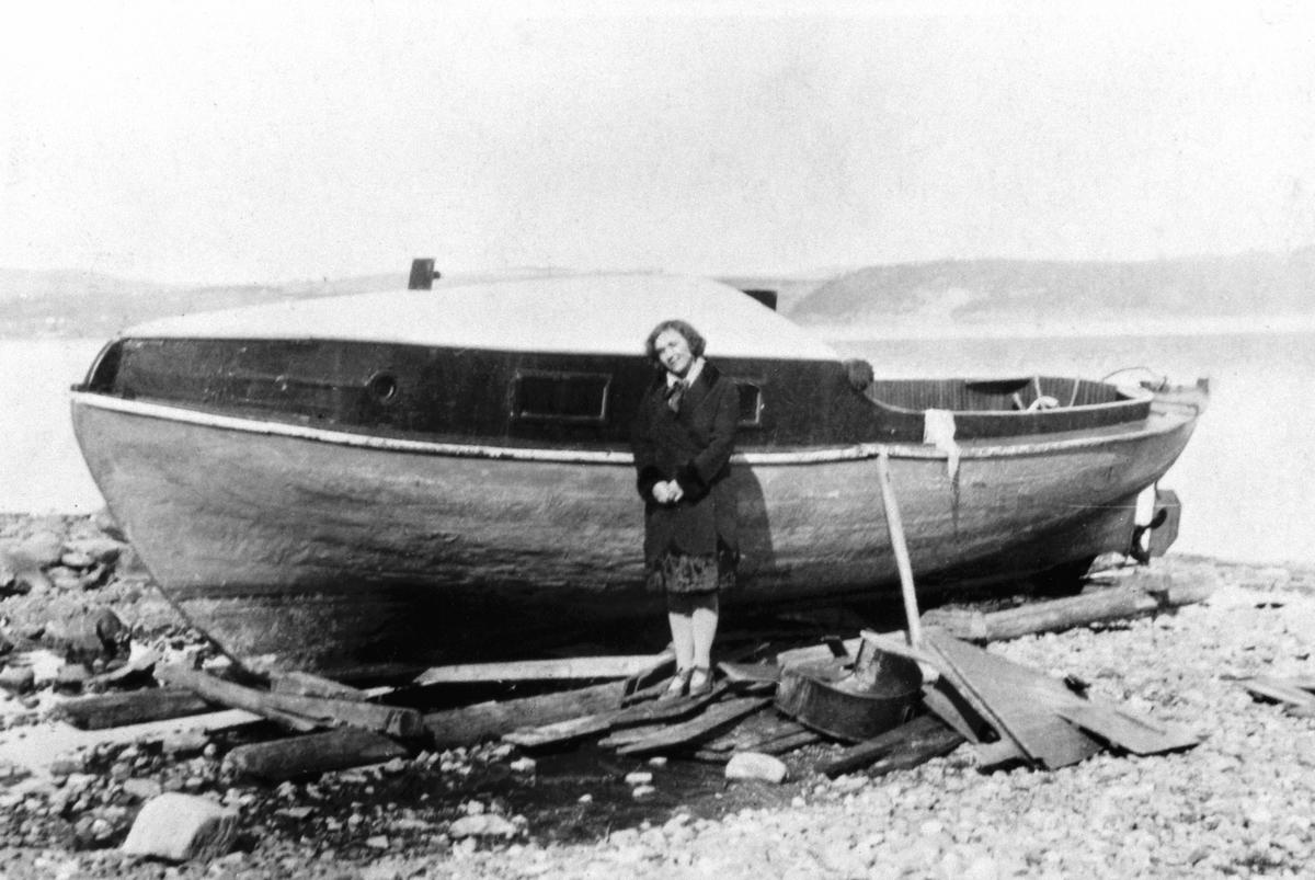 Dame ved motorbåt på Mjøsstranda, Grefsheim, Nes, Hedmark. Båten er M.B Karine som tilhørte Grefsheim.