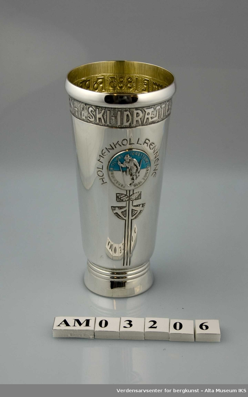 """Form: Konet, med emaljert, rundt emblem i blått,hvitt,sølv Pokalens emblem er av en skiløper og teksten """"Foreningen til skiidrettens fremme 1883"""