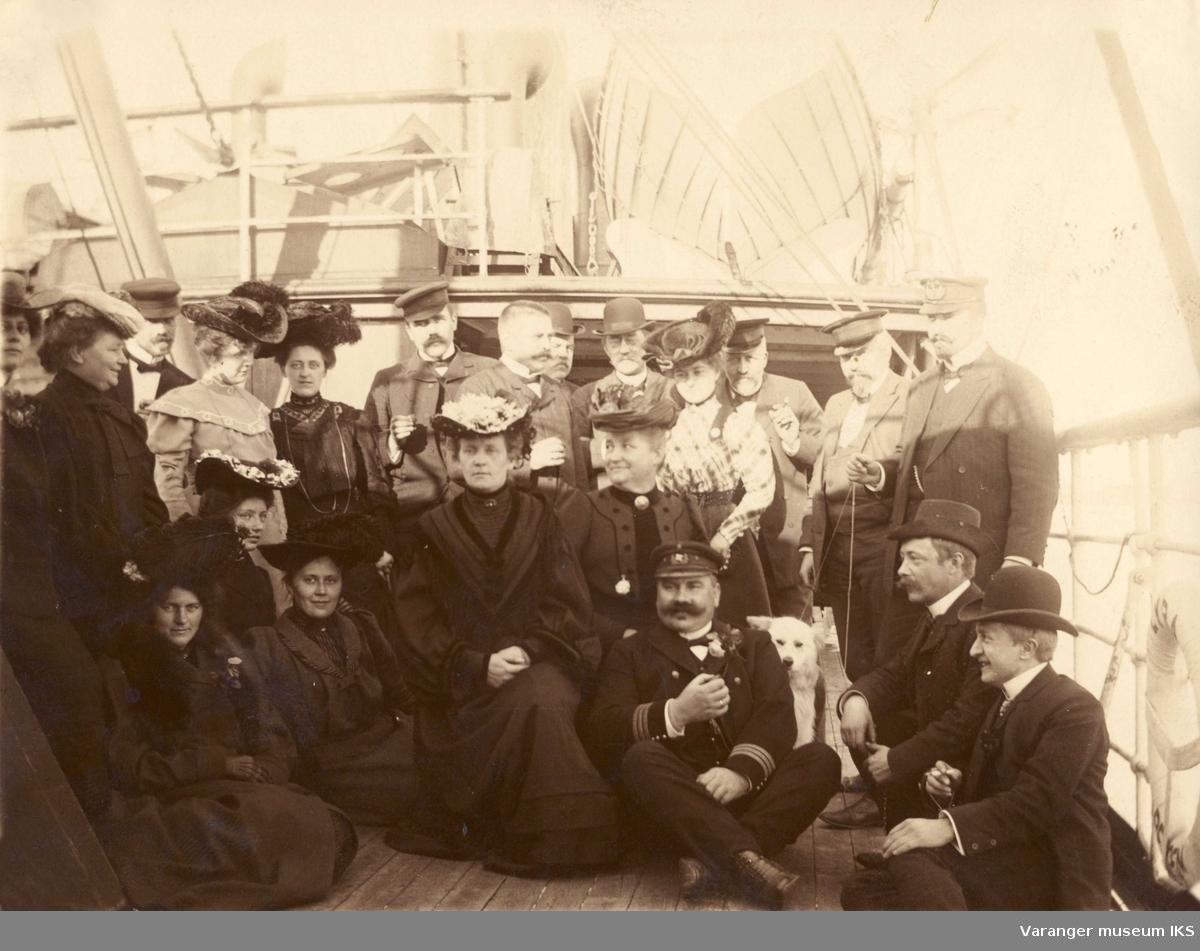 Gregaards forlater Vadsø. Damer med hatter, menn med uniform og hund på dekk på båt