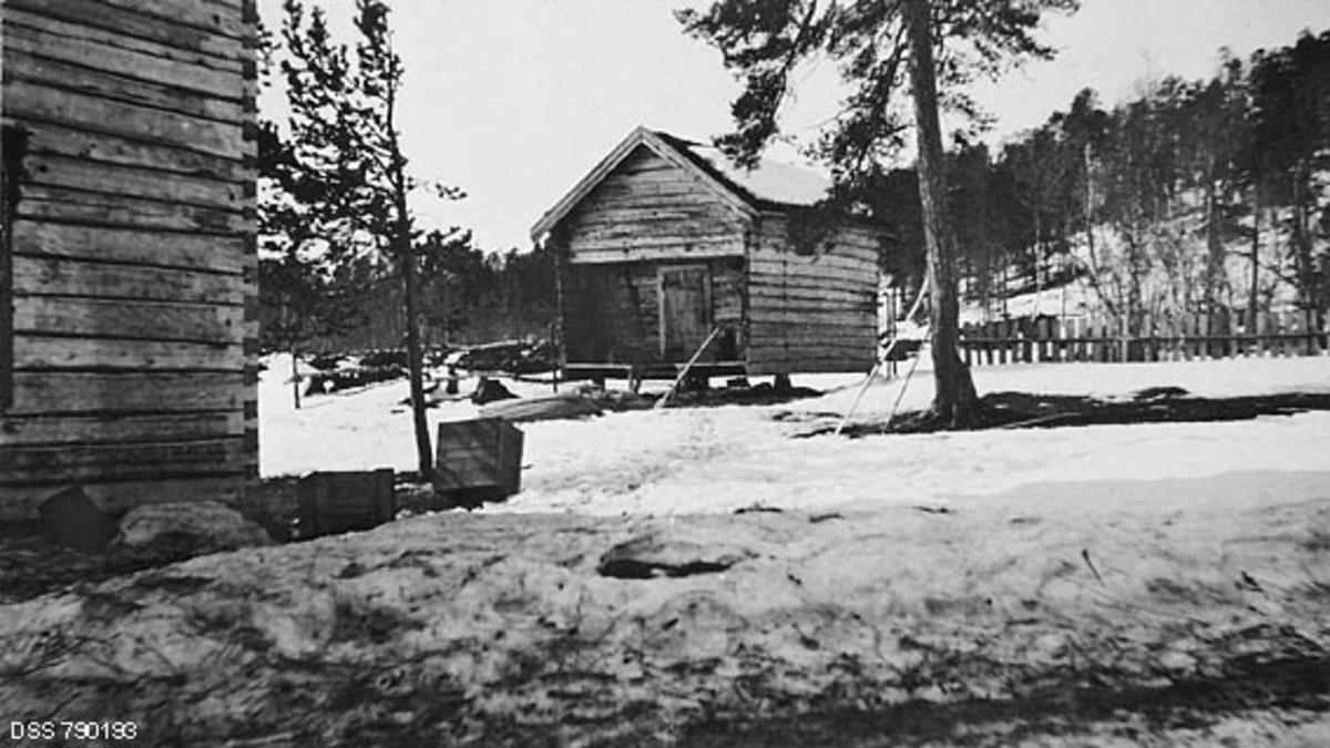Fra gardstunet på skogvoktergarden Nesheim i Pasvikdalføret i Finnmark.  Fotografiet viser først og fremst stabburet, et laftehus med rektangulært grunnplan og som kviler på fire stabber, plassert under kryssingspunktene for tømmerveggene.  Her har tømmermennene valgt en sinklaftløsning.  Inngangsdøra befinner seg på den gavlveggen som vender mot fotografen, litt inntrukket under det tømrete røstet.  Ei lita tretrapp fører opp mot plattingen foran inngangsdøra.  I snøen foran stabburet ligger en pulk med undersida oppovervendt, antakelig med henblikk på at den ikke skulle fylles av snø om det kom nedbør.  I forgrunnen ser vi hjørnet av en annen sinklaftet bygning.  I snøen på bakken ligger det et par trekasser og ei sinkbøtte.   Den gamle skogvoktergarden Nesheim ble herjet av brann 16. april 1909.  Bebyggelsen var forsikret for 1 650 kroner.  Ettersom mulighetene for å drive jordbruk ved skogvokterboligen hadde vist seg vanskelige, bestemte etaten at skogvoktergarden skulle gjenoppbygges ved Galgonjarg, cirka tre kilometer fra det opprinnelige anlegget.  Gjenoppbygginga tok tid.  Først i 1911 var det «nye Nesheim» ferdig.  Anlegget skal ifølge skogvalteren i distriktet ha fått en noe «større stil» enn det som ble ødelagt av brann, noe som også forklarer at byggekostnadene oversteg både den nevnte brannforsikringssummen og budsjettet på 1 800 kroner.  Endelig byggesum ble 2 112, 03 kroner. Stabburet på bildet er altså bygd i 1910-1911, og det var følgelig bare to-tre år gammelt da dette fotografiet ble tatt.