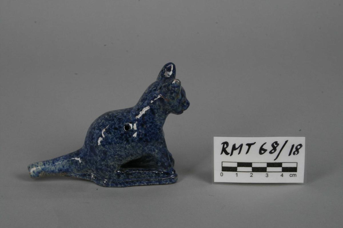 Spaltefløyte i brent, blåglasert leire. Utformet som en katt. Blåsehull i halen, på hver side av ryggen et fingerhull.