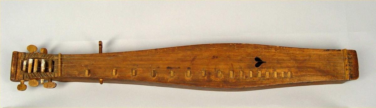 Instrument er laget i nåletre, utskåret fra ett stykke, inklusiv hode og skruekasse. Enkelt hode, ingen bunn, 5 stemmeskruer (løvtre - eik?) i skruekasse samt én i venstre sargen. Et lydhull i form av hjerte, dekorasjoner i form av 1-3 rissete linjer i lokk og sargen, skåret mønster i skruekassens kanter (diagonalt tøy/bølge-formet).  6 strenger i messing hverav en kortere (festes gjennom lokk mot den separate stemmeskruen, sannsynl. mangler denne pyramide. Instrumentet har ikke strengeleder, strenger festes direkte etter stol i messingskroker som er festet gjennom lokk/bakstykke. 16 noter, sadel og stol i samme material som stemmeskruer.
