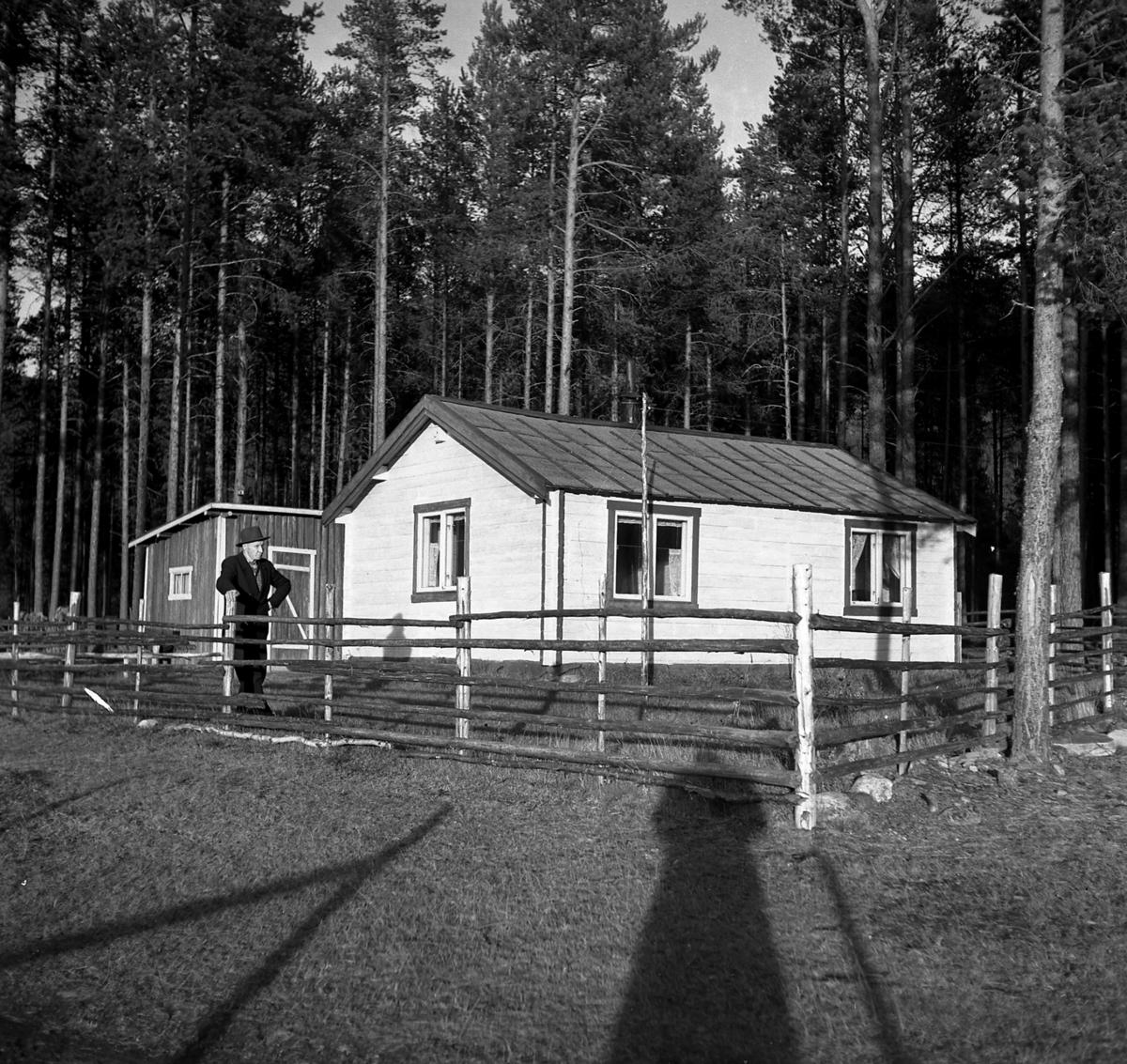 En mann foran hytte