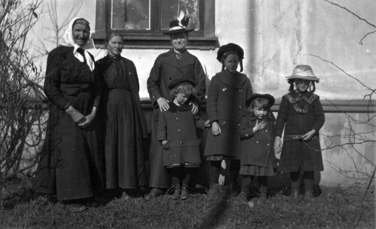 Gruppe ukjente kvinner og barn foran et hus.