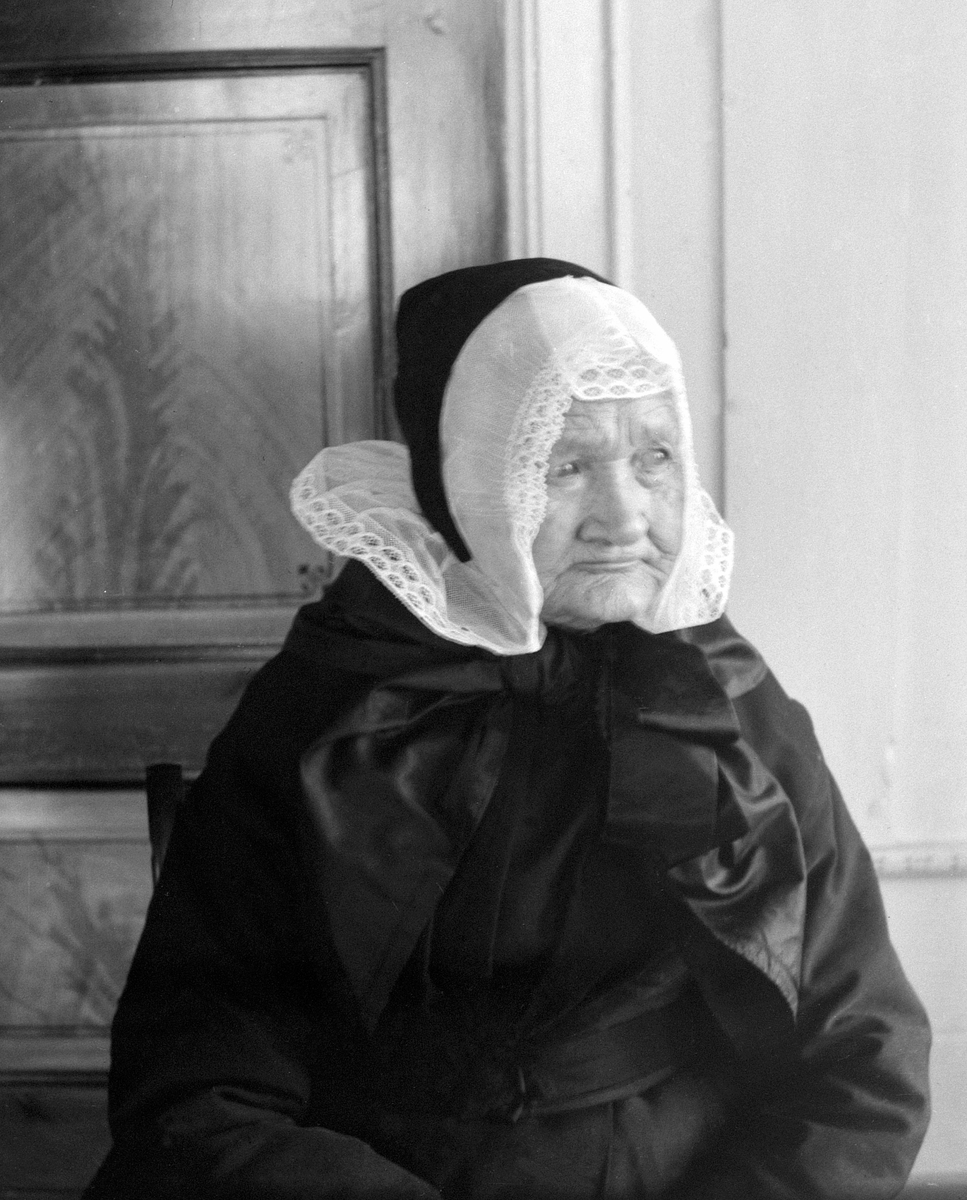 MARTHE LØKEN, F. 1831, FØDERÅDSKONE PÅ LØKEN ØSTRE på Rudshøgda i Ringsaker, SKRUVELUE, KVINNEDRAKT.  Marthe Løken født på Biri i 1831. Her er hun fotografert på sine eldre dager på Løken Østre i Veldre. Der levde hun som enke og føderådskone til hun døde i 1909. Hodeplagg, skruvelue.
