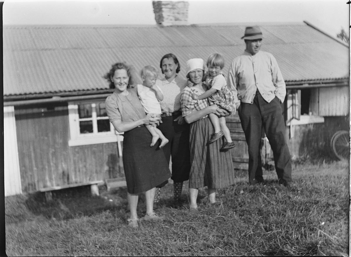 Ukjent gruppe kvinner, barn og en mann utenfor ei hytte.