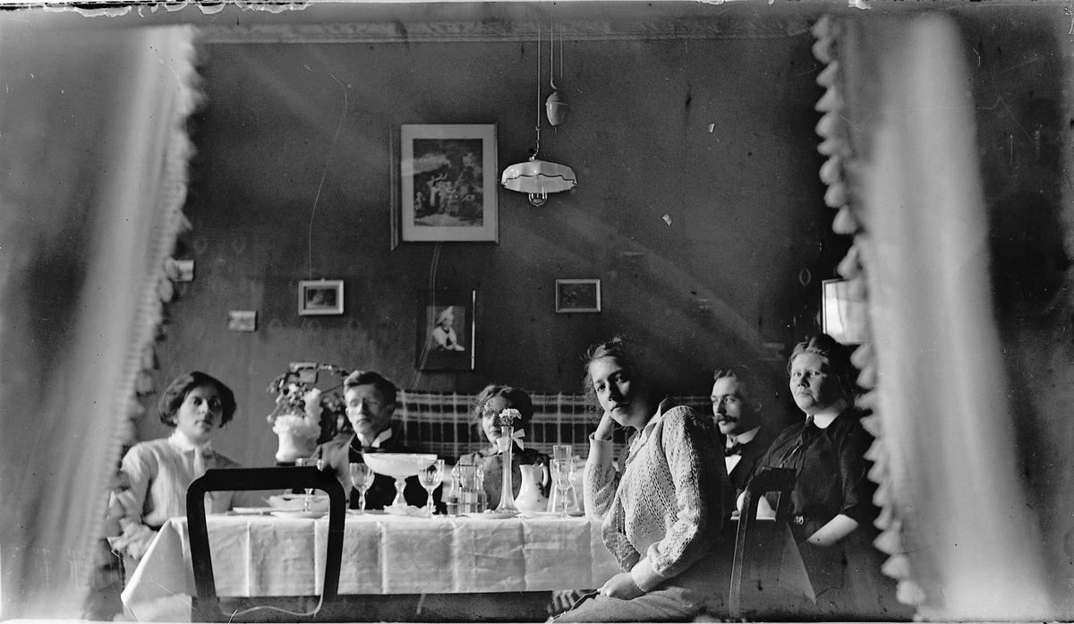 Interiør, stue. Til venstre sitter Louise Johannessen. De øvrige ukjente.