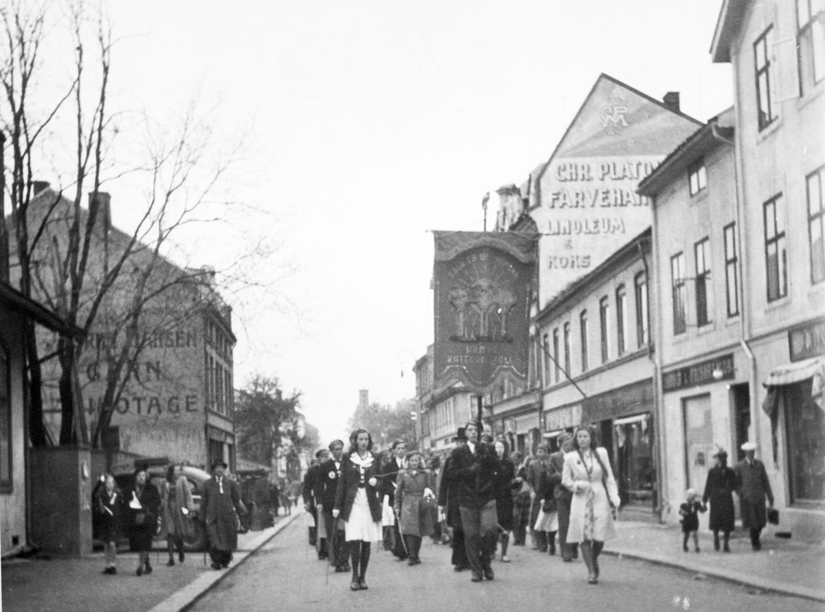 Skoletoget passerrer gjennom Torggata 17. mai 1945. Fredsdagene etter 2. verdenskrig. Elever, russ fra Hamar katedralskole. Skolefane.