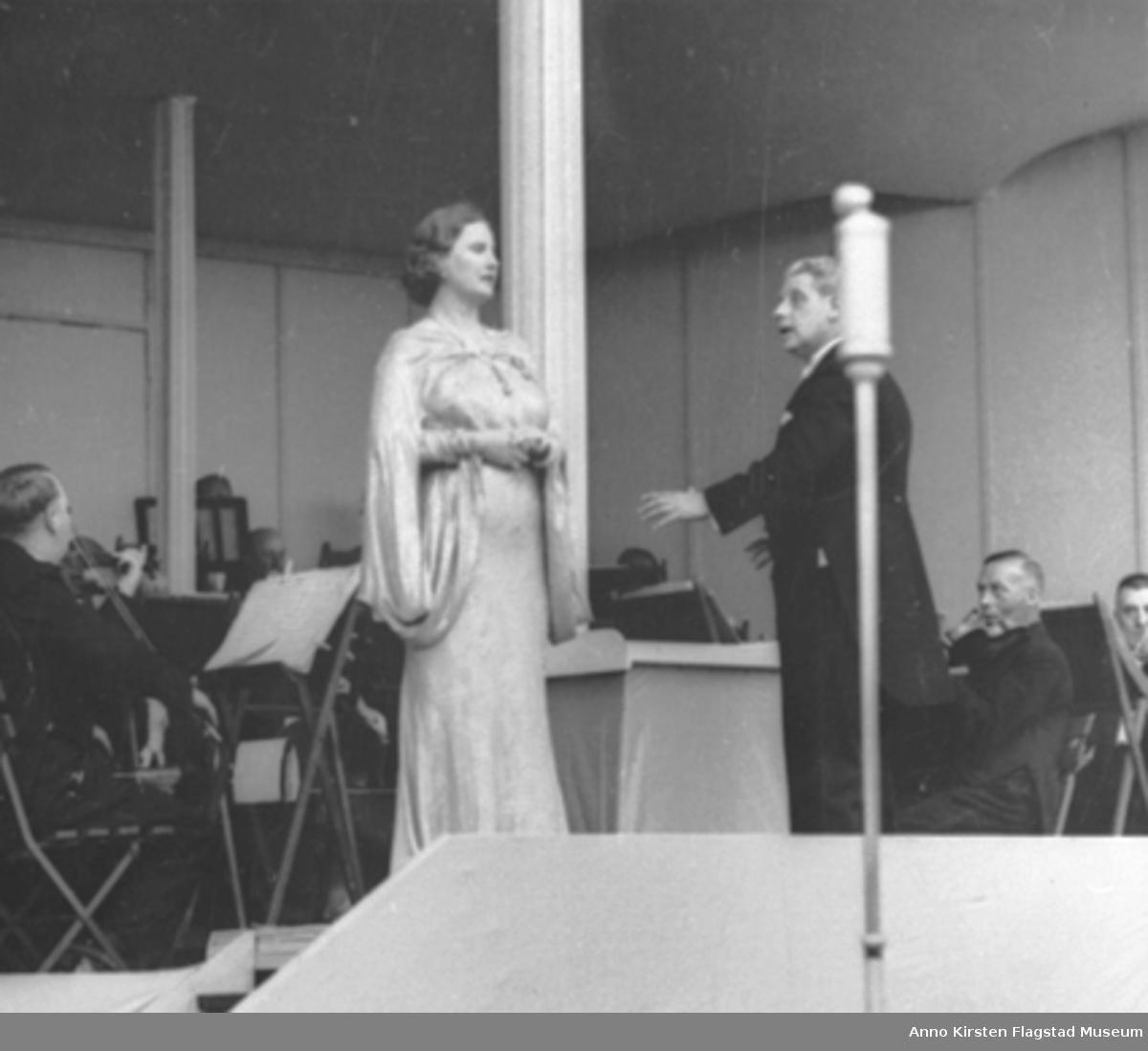 Kirsten Flagstad ved friluftskonserten på Frogner Stadion, Oslo 7. juli 1937. Dirigent Ole Flagstad. Konserten samlet 15 000 tilhørere. Kirsten Flagstad at the open air concert at Frogner Stadion, Oslo 7 July 1937. Conductor Ole Flagstad. Audience of 15 000.