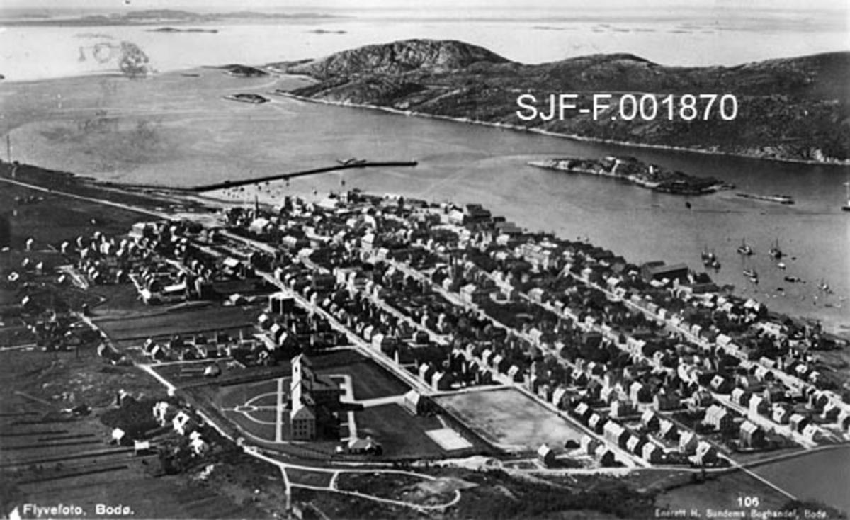 Flyfotografi av byen Bodø i Nordland, antakelig fra 1930-åra [se fanen «Opplysninger»].  Fotografiet viser bykvadraturen med boligområder i på landsida og næringsbygg og kaier mot sjøen.  De nyere boligområdene i Østbyen og Vestbyen later fortsatt til å ha vært ubebygde.  I forgrunnen, litt til venstre for bildets midtakse, ligger en stor bygning omgitt av en park, antakelig sentralsjukehuset i Nordland.  Vi ser også hvordan det er bygd en molo i sundet utenfor byen, antakelig for å skjerme havneområdet.  En del mindre fartøyer ligger for anker utenfor kaiene.  Øyene på motsatt side av sundet later fortsatt til å være nesten ubebygde.  Mye av den bebyggelsen vi ser på dette fotografiet ble ødelagt etter krigshandlinger i mai 1940.