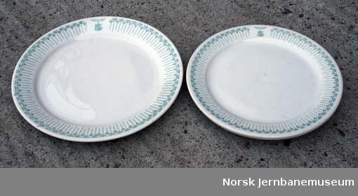 """Dekketøy med logo """"NSS"""" og grønn mønstret bord: flate tallerken og askjett"""