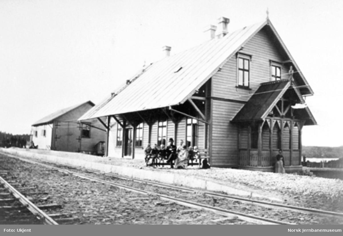 Prestebakke stasjon med stasjonsbygning og uthus; en familie sitter på benken på plattformen